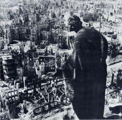 ドレスデン市役所の屋上に建つ砂岩の彫像が廃墟と化した市街を見下ろしている)